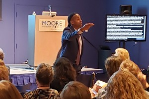 Speaker talking to audience at Moore Art Education event.