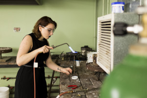 Student with blow torch working on metal project
