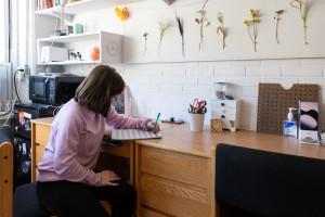 student sitting at desk in dorm room