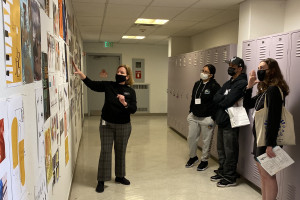 professor showing work on wall to three people