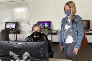 student sitting at computer with parent looking on behind them
