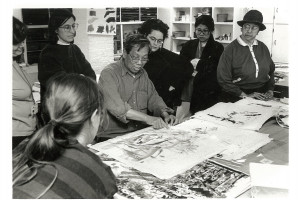 Professor Chen Lok Lee, in glasses and with sleeves rolled up, is before a table pointing to a work of art, surrounded by six people.