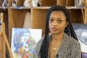A young black woman with long braids and gold hoop earrings and wearing a black and white patterned blouse sits in front of artwork and easels in an art classroom.