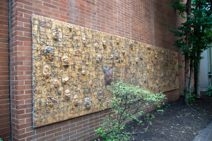 Photo of Black Lives Matter wooden mural by John Costanza with faces protruding out of surface mounted on a brick wall in the Moore Galleries coutryard
