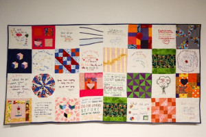 A 24-panel quilt designed by Rachel Wallis MA '16 called Inheritance features panels in white, red, green and purple fabrics that include embroidered words.