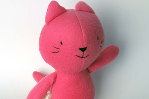 "A small, pink plushie cat with its arm raised. Its tag says, ""Hi! I'm Rose!"""
