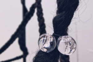 Image is a detail of an installation by artist Ashley Gunter that shows synthetic braided Black hair with hair bobbles wrapped around a wooden frame. The title of the 2019 piece is Holding Space.
