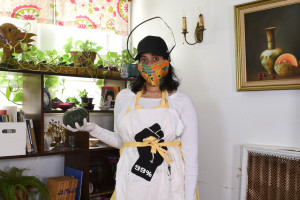 Alicia Grullón wearing a mask and a hat holding a squash and looking towards the viewer in front of a shelf with books, plants and family photos