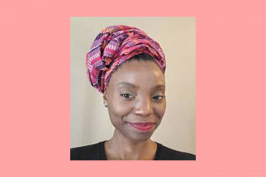 A black woman is wearing a black shirt and is wearing a red, purple and orange head wrap.