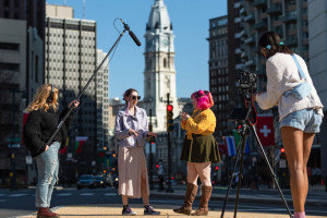 Four young filmmakers standing on the Benjamin Franklin Parkway with City Hall in the background. One holds a boom mic, one stands behind a camera on a tripod, and the two in the middle are in animated conversation.