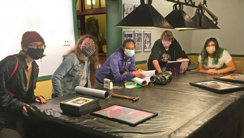 Five Moore students wearing masks are gathered around a covered pool table topped with framed art and rolled up pieces of art that they are readying to hang.