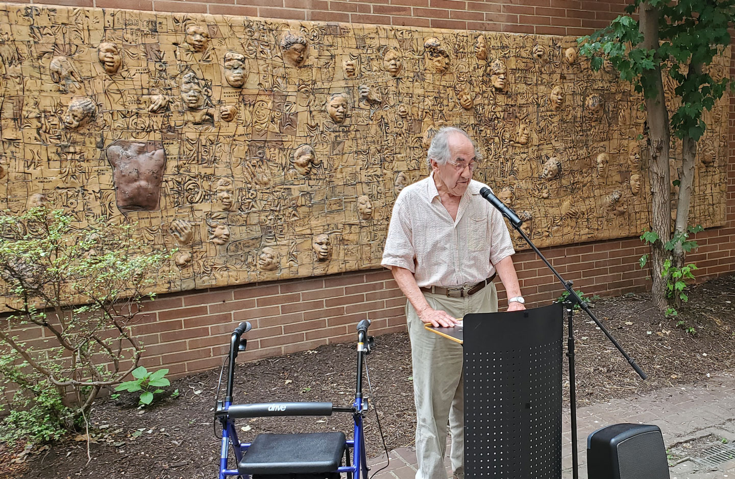 Photo of John Costanza speaking in front of his Black Lives Matter mural at the dedication in the Moore Galleries courtyard