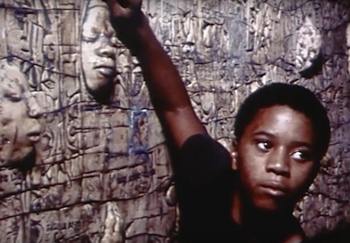 Screenshot of a young Black boy standing in front of John Costanza's Black Lives Matter Mural