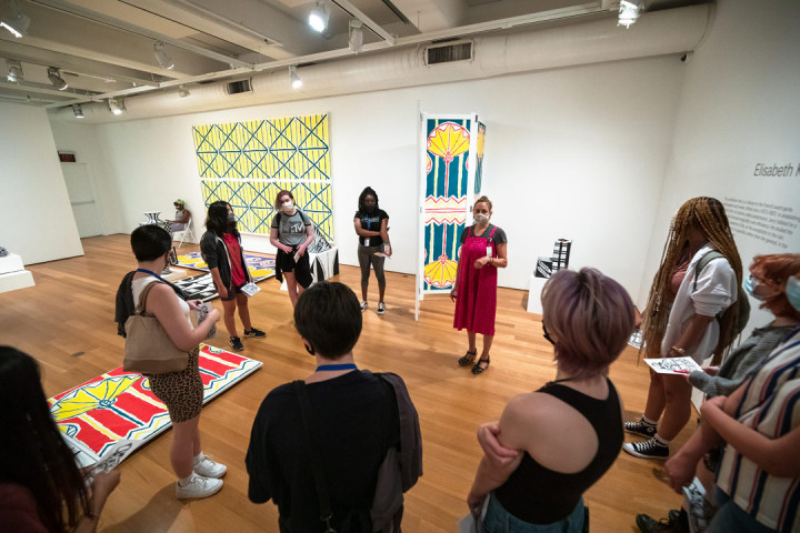 A woman wearing a mask speaking to SADI 2021 students gathered around her in the Fabric Workshop and Museum gallery