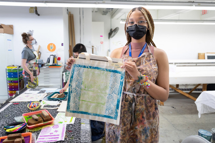 A SADI 2021 student showing her artwork on a tote bag at the Fabric Workshop and Museum
