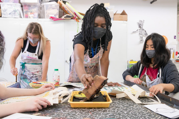 Three SADI 2021 students working on their art at the Fabric Workshop and Museum. The student in the middle is reaching out to add ink on their stamp.