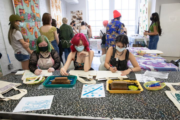 Three SADI 2021 students drawing their designs on tote bags with other students behind them at the Fabric Workshop and Museum