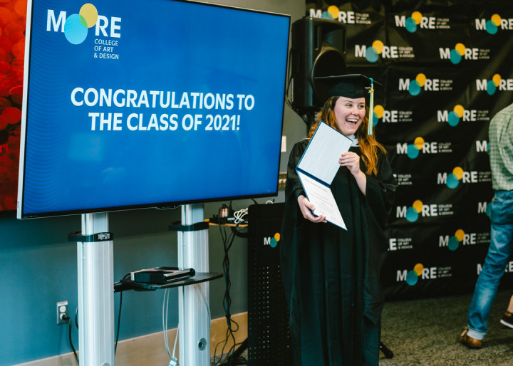 """Kelly Marrone holding up her diploma and smiling in front of a screen saying, """"Congratulations to the class of 2021!"""""""