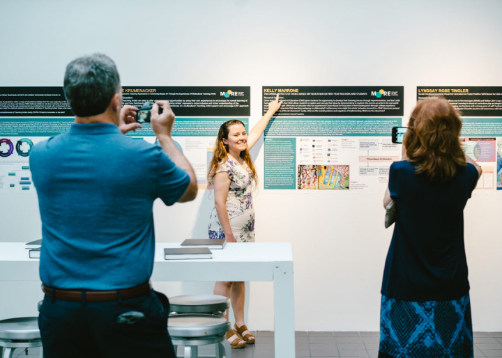 Photo of Kelly Marrone pointing at her thesis presentation at the Art Education 2021 Commencement
