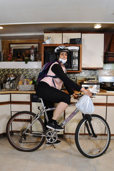 Alicia Grullón wearing a mask and helmet and backpack on a bike in her kitchen