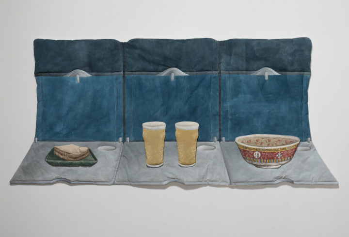 Photo of Kay Healy's soft sculpture Fabric Objects with a sandwich, two glasses of beer and a bowl of soup on a couch