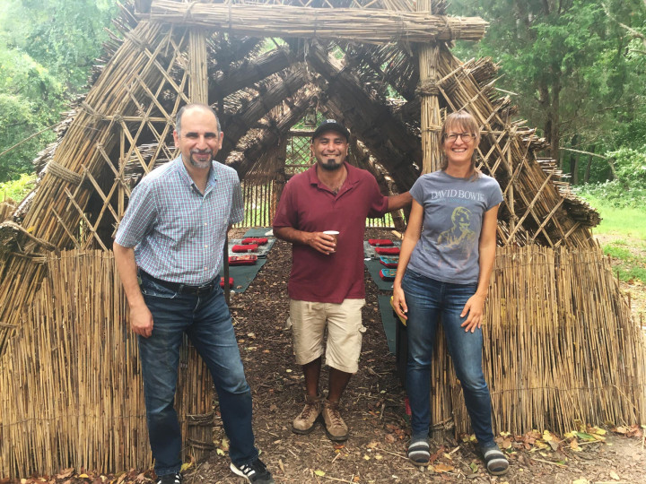 Three people posing for a photo in front of a wooden structure