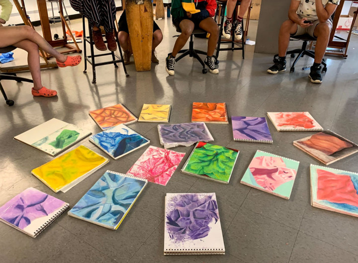 YAW student paintings displayed on the ground for review